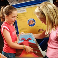 Two girls are standing around a exhibit that has a yellow and blue information panel at the back. In the centre of the group is a model volcano.