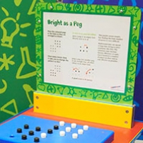 An exhibit table with a information panel, sits in front of two walls. On the table lays a rectangle shape with pegs sitting on top.