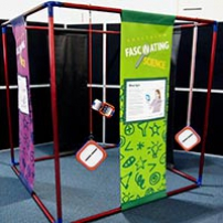 A large blue and red cube frame that has purple and green information banners hanging between top and bottom bars of the cube. There are also square orange and white shapes hanging from the frame.