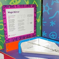 A red and blue exhibit table, with an orange, whih and purple information panel on top, sits in front of two green and blue walls. On the table top are two blue framed mirrors at right angles to one another.