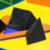 On top of the yellow surface sits a flat orange triangle base and four black triangular pieces.