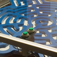 A large blue and white flat maze that is contained within a blass and steel display case.