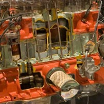 A full scale petrol combustable engine with cut away areas, showing the cylinders and pistons, all encased in a perspex box.