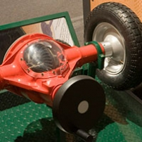 A black and green display base that has a red, car differential with a see-through window to show the gears.