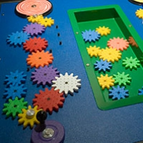 On blue surface, sits multiple different coloured and sized gears, interlinked and sitting in a green tub.