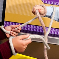 Two ropes intertwined between two sets of hands.