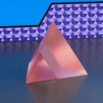 A pink pyramid in two halves sitting in a black surface.
