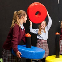 4 school girls standing behind 3 black poles that have colourful large yellow, red and blue rings threaded on each pole.