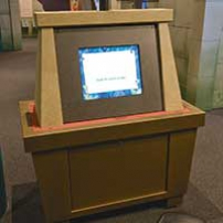 A brown exhibit table with a vertical dispaly area that has a monitor screen.