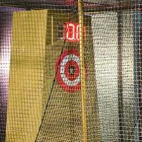 A red and white builseye target sits on a yellow stand behind netting.