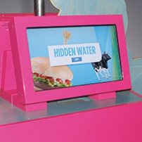 A pink monitor with the words 'Hidden Water', a hamburger and a cow on the screen.