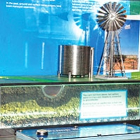 A beige coloured table with a blue information panel in the background. On the table is a scale model of a water pump and water tank.