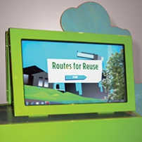 A green display table with a matching green monitor siting on top. The picture of houses and trees on the monitor as the title 'Routes for Reuse'.