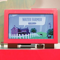 A red exhibit table with a matching red monitor on top. The picture on screen is of a purple house behind a white picket fence, and the title ' Water Farmer' at top of screen.