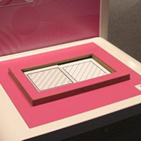 Two squares with diagonal lines appear on a table top that is pink and cream in colour.