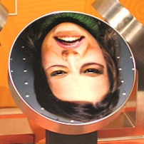 A woman's face printed upside down onto a metal disc