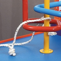 An orange and blue exhibit table. Red yellow and blue steel bars rise out of the table top, and are bent into different shapes. A piece of white rope with a knot in it is threaded between the bars.