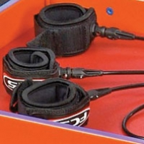 An orange tray with three black velcro handcuffs that have cords between them.