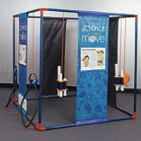 a blue, black and white cube structure that has vinyl blue and white information panels from top to bottom with spaces in between. There are also different sound exibits hanging from orange cord from the cube structure.