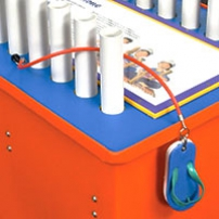 An orange and blue exhibit table with a white information panel laying flat on the top, two rows of 20 millimetre pvc piping rising up from the table top, and a blue thong attached to an orange cord hanging over the table side.
