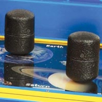 Two black weights sitting on a table top with picutres of Earth and Saturn under them.