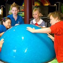 Primary aged children with hands on a large blue orb exhibit.