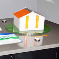 A model house with a flip lid roof demonstrating how wind flows around a house.