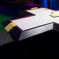 A cross shaped black and yellow air hockey table with a white surface.