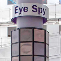 A large pilar within a large white foyer, with different pictures of eyes on the pilar. The words 'Eye Spy' is on at sign at the top of the pillar.