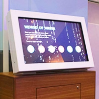 A computer monitor on top of a timber display unit.