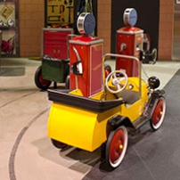 A yellow ride on toy car with red wheels parked along side replica toy red petrol bowsers.