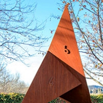 A rusted metal sculpture with six faces located in a garden environment.