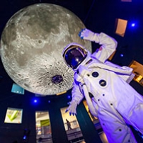 An astronaut standing underneath The Moon exhibit