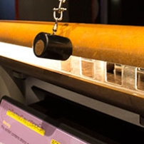 Copper and perspex tube sitting on two metal legs and a purple and yellow information panel