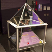 A stainless steel exhibit, with a pyramid on the top and pruple and yellow information panels