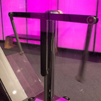 Three metal arms pivoting on a single metal mechanism, behind a clear perspex case
