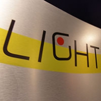 A stainless steel sigh with a yellow splash of colour and the word 'LIGHT' in black written across it