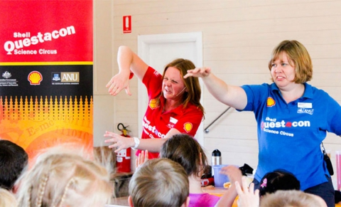 Two women in red and blue shirts performing to a audience of primary school students.