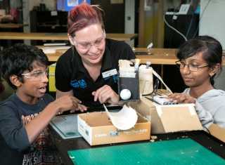 A Questacon presenter and two holiday workshop participants build a robot