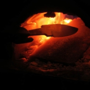 A steel knife, almost complete, is placed into a hot furnace filled with white hot ash and flame