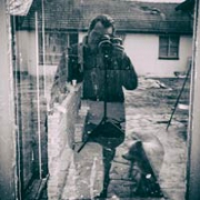 Man, peering through a camera, takes a photo of his reflection in a window.  A dog stands impatiently beside him.