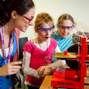 A Questacon facilitator shows off a printed box created by a 3D printer to two young girls