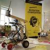 A robot in front of an Invention Convention Banner