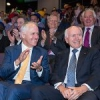 Prime Minister Malcolm Turnbull sitting with John Howard with crowd looking on