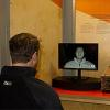 A man looks at a video screen displaying facial recognition software identifying parts of his face.