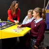 A woman explains an exhibit to two school girls
