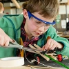 A boy in green builds a contraption