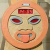 A round orange face with a clock on the top