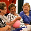 3 elderly women sitting down with one holding a pink balloon.