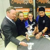 Minister Pyne building flying cups over a wind table with three students